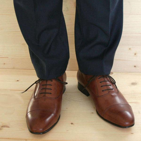 Foto von Herrenbeinen im grauen Anzug mit zwei braunen Oxford Glattleder Herrenschuhen mit Zehenkappe. Modell Oxford first