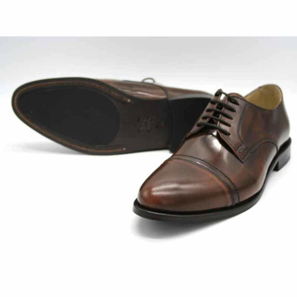 Foto von zwei braunen, schwarz changierenden Herrenschuhen einer auf der Seite liegend, so dass die durchgenähte Sohle zu sehen ist - Modell Premium Klasse 329