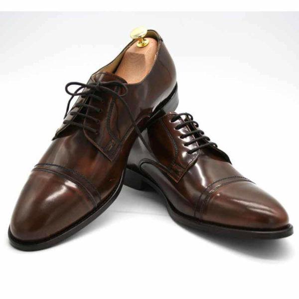 Foto von zwei braunen, schwarz changierenden Herrenschuhen einer mit Schuhspanner mit goldenem Knauf, der rechte auf den linken Schuh gestellt - Modell Premium Klasse 329