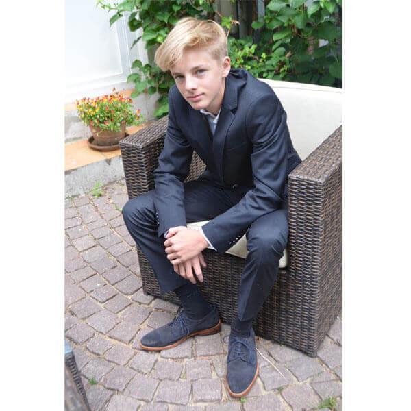Herren Schuhe dunkelblau Foto junger Mann sitzend in blauem Anzug und mit blauen Wildlederschuhen Modell Legere elegant