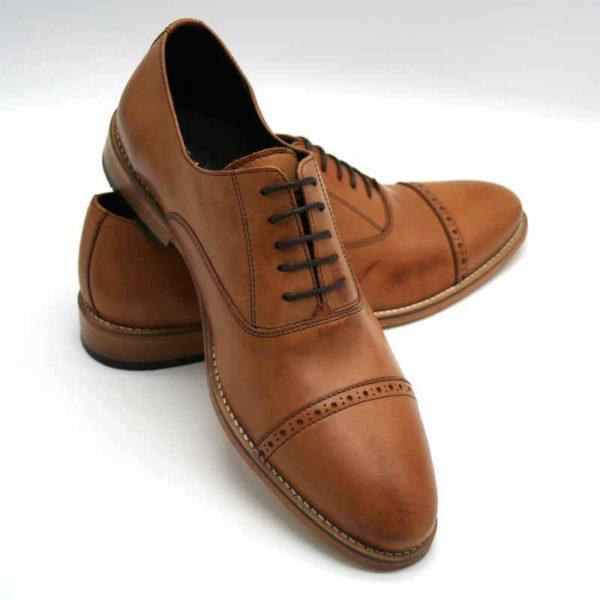 Foto von 2 Herrenschuhen Modell Oxford in Perfektion. Der rechte Schuh stützt sich auf den Linken. Eine Spitze nach vorne weisend. Modell 371