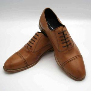 Foto von 2 Herrenschuhen Modell Oxford in Perfektion. Der rechte Schuh stützt sich auf den Linken. Spitzen sind nach vorne auseinander weisend. Modell 371