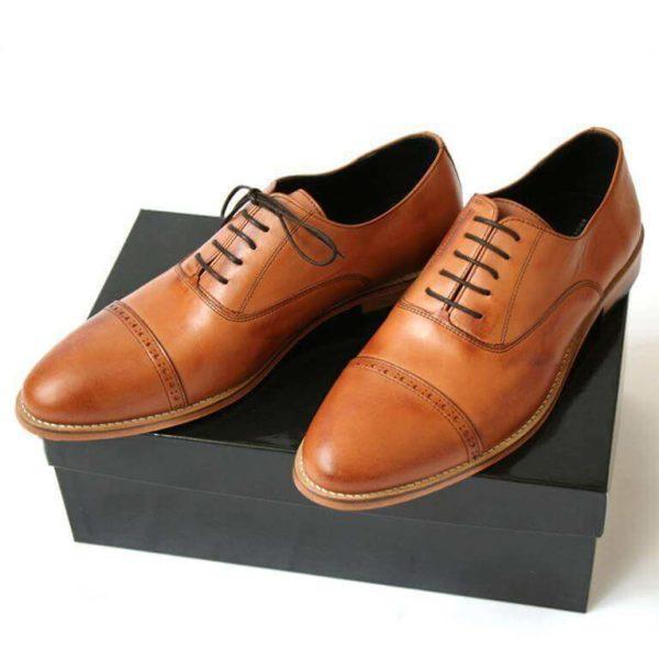 Foto -Zwei Herrenschuhe mit Oxford Schnürung in Brandy auf schwarzem Schuhkarton. Modell: Oxford in Perfektion-371