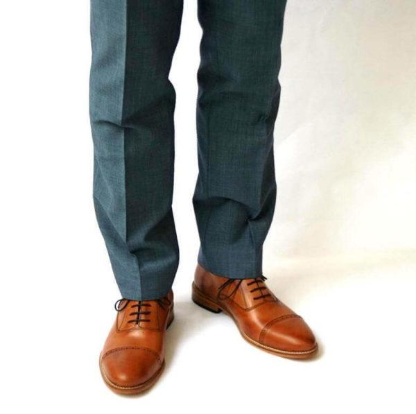 Foto-Zwei Herrenschuhe mit Oxford Schnürung in Brandy und Anzughosenbeine - Frontalansicht. Modell: Oxford in Perfektion-371
