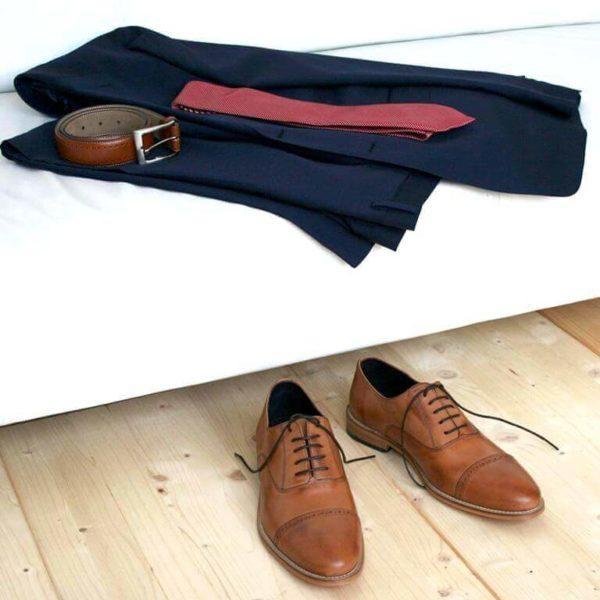 Foto-Zwei Herrenschuhe mit Oxford Schnürung in Brandy vor weißer Couch mit dunkelblauem Anzug, Krawatte und Gürtel. Modell: Oxford in Perfektion-371