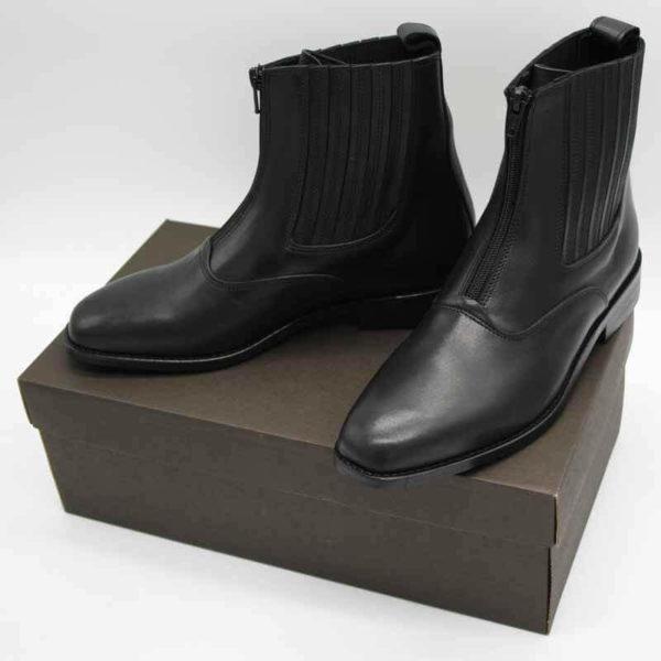 Foto von zwei schwarzen Stiefeletten mit Reißverschluss vorne und flachem Absatz auf dunkelbraunem Schuhkarton. Modell: 411-Schwarze Stiefelette_1