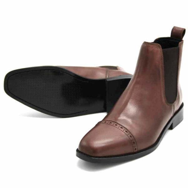 Foto von zwei braunen Chelsea Stiefeletten. Eine liegend, so dass die schwarze Laufsohle erkennbar ist, die andere stehend nach vorne zeigend. Modell: 421-Chelsea Braun_2