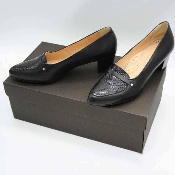 Foto von zwei schwarzen Pumps mit Schlangenmuster an der Spitze auf dunkelbraunem Schuhkarton stehend. Modell 511 Elegante Damenschuhe 1