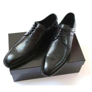 Foto-Schwarzer Halfbrogue Business Schuh mit Perforation. Ansehnlich und stilvoll. 2 Schuhe auf schwarzem Schuhkarton.