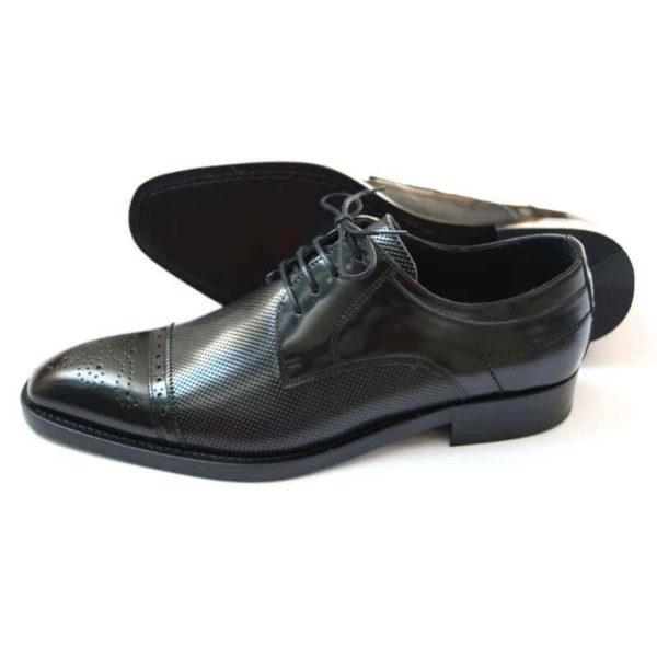 Foto-Business Herrenschuh in Schwarz aus perforiertem Leder. Ein Schuh zeigt nach links der andere liegt, so dass die Sohle zu sehen ist.