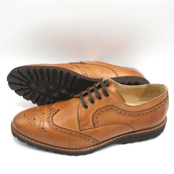 Budapester Cognac elegant, solide Herrenschuhe. Ein Schuh liegend, so dass die Gummiprofilsohle sichtbar ist, der andere stehend, nach links zeigend. Modell 372