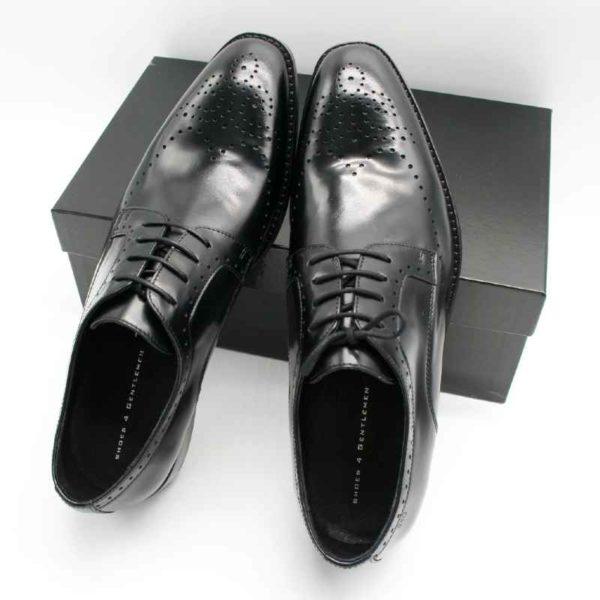 Foto zeigt Derby Herrenschuhe, die beide an einen schwarzen Schuhkarton angelehnt sind_Modell 308