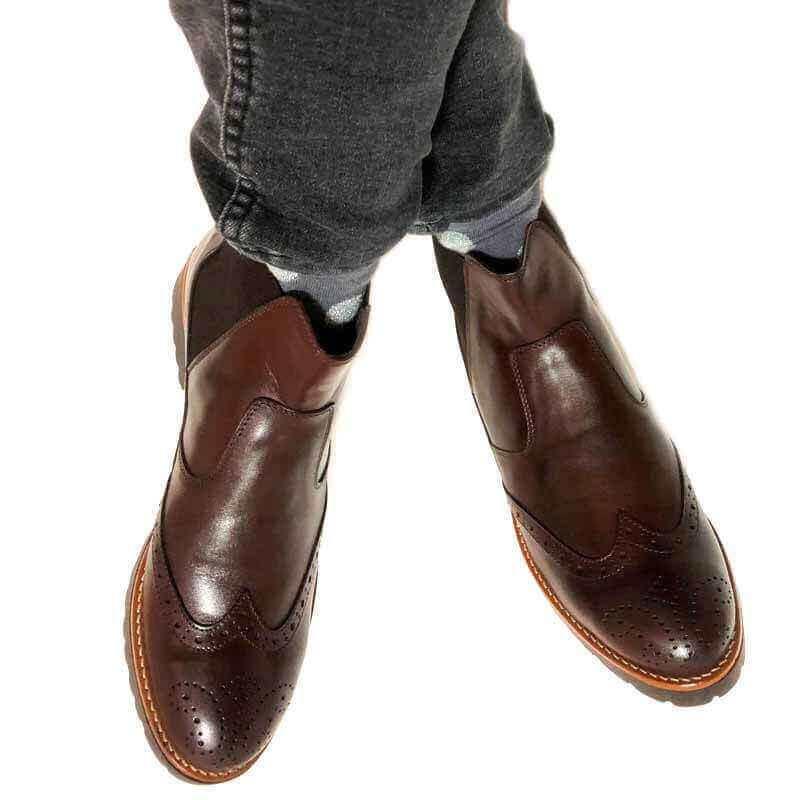 Foto Dunkelbraune Chelsea Boots an Füßen. Beine übereinandergeschlagen_Modell 620