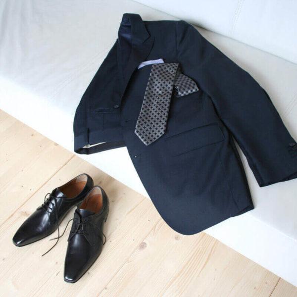 Foto 2 schwarze Herrenschuhe Elegant und schlicht Glattleder vor einer Couch auf der ein Anzug mit Krawatte liegt