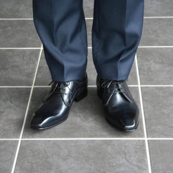 Foto 2 schwarze Herrenschuhe Elegant und schlicht Glattleder. Forntalansicht mit Anzugbeinen in Dunkelblau.