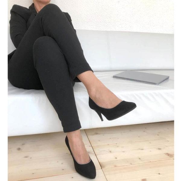 Foto Elegante Pumps schwarz Rauleder mit Metallapplikation an Damenbeinen sitzend auf weißem Sofa mit schwarzem Hosenanzug_Modell 515