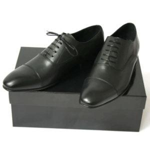 Foto von zwei schwarzen Glattleder Oxford Herrenschuhen auf schwarzem Schuhkarton. Modell Erste Wahl