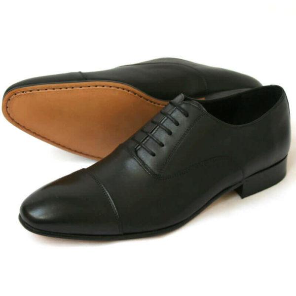Foto von zwei schwarzen Glattleder Oxford Herrenschuhen nach links zeigend - ein Schuh liegt auf der Seite, so dass die Sohle zu sehen ist. Modell Erste Wahl