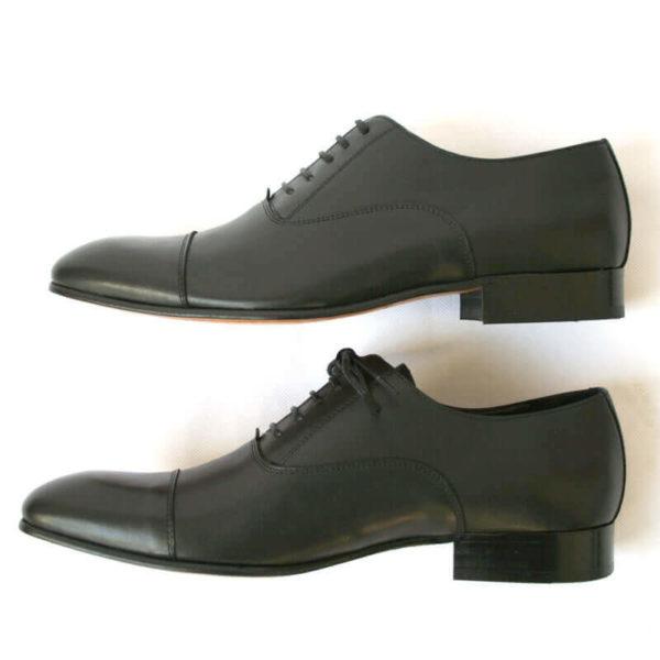 Foto von zwei schwarzen Glattleder Oxford Herrenschuhe übereinander nach links zeigend. Modell Erste Wahl