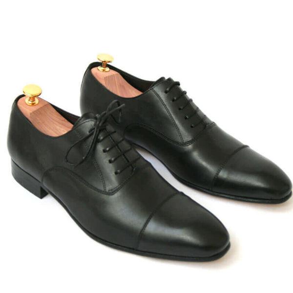 Foto von zwei schwarzen Glattleder Oxford Herrenschuhen nach schräg unten rechts zeigend mit Goldkopf-Schuhspannern. Modell Erste Wahl