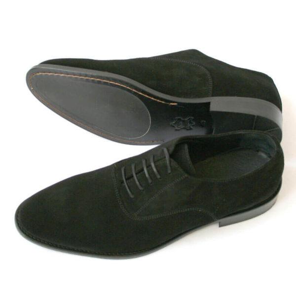 Foto von zwei schwarzen Wildleder Oxford Herrenschuhen nach links zeigend - ein Schuh liegt auf der Seite, so dass die Sohle zu sehen ist. Modell Herren Oxford