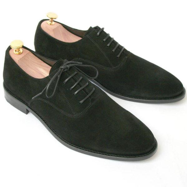 Foto von zwei schwarzen Wildleder Oxford Herrenschuhen nach schräg unten rechts zeigend mit Goldkopf-Schuhspannern. Modell Herren Oxford