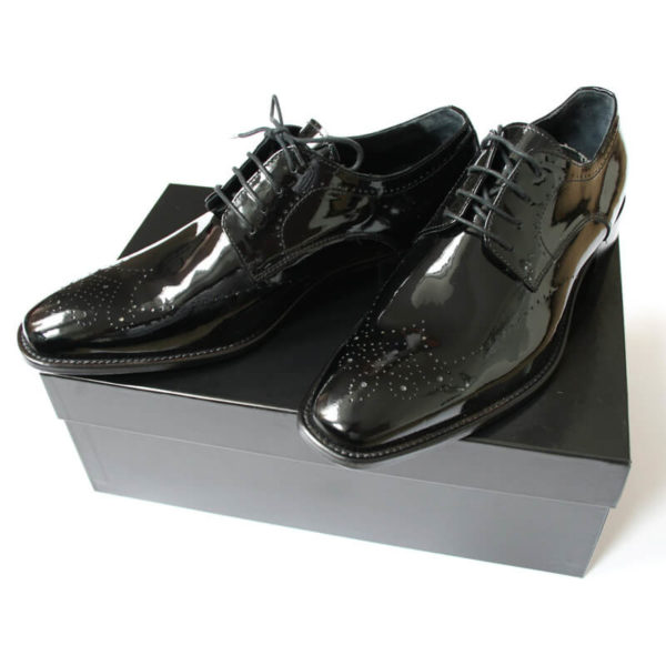 Foto Edler Abendschuh. Es werden zwei schwarze Herren Lackschuhe gezeigt; beide nach links zeigend auf schwarzem Schuhkarton. Modell 211