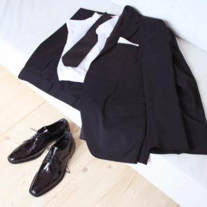 Foto Edler Abendschuh. Es werden zwei schwarze Herren Lackschuhe vor weißer Couch gezeigt auf der ein dunkler Anzug liegt.. Modell 211