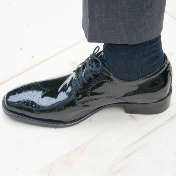 Foto Edler Abendschuh. Es wird ein schwarzer Herren Lackschuh am Fuß gezeigt; Socke und unteres Hosenbein sind auch zu sehen. Der Schuh zeigt nach links. Modell 211
