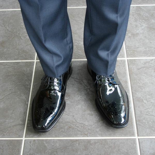 Foto Edler Abendschuh. Es werden zwei schwarze Herren Lackschuhe und Herrenunterschenkel mit dunkelblauem Anzug gezeigt; beide nach vorne weisend. Blick von oben gegenüber. Modell 211