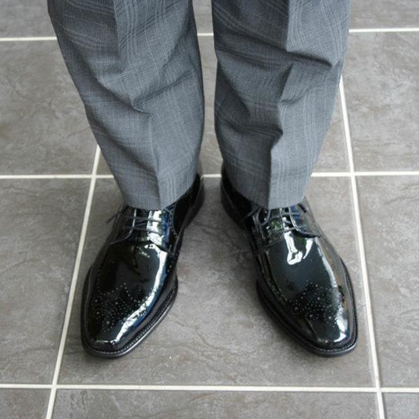 Foto Edler Abendschuh. Es werden zwei schwarze Herren Lackschuhe und Herrenunterschenkel mit grauem Anzug gezeigt; beide nach vorne weisend. Blick von oben gegenüber. Modell 211
