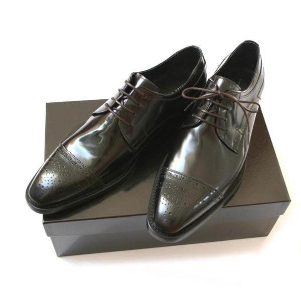Foto Repräsentative Eleganz. Eleganter Halfbrogue Business Schuh. 2 Schuhe auf schwarzem Schuhkarton.