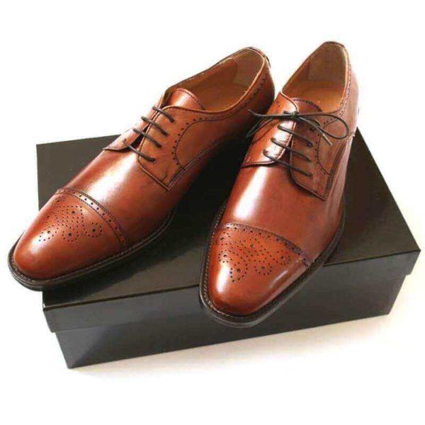 Zwei cognacfarbene Herrenschuhe mit Zehenkappe auf schwarzem Schuhkarton. Modell Topmodischer Allrounder-232-1