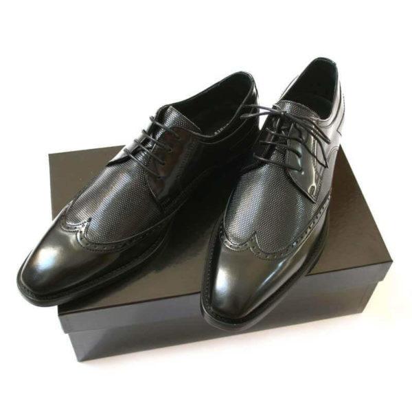 Foto Weltmännischer Schnürer. Eleganter Derby Business Schuh mit Muster. 2 Schuhe auf schwarzem Schuhkarton.