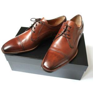 Foto Individuell und maskulin Herrenschuh Business Derby in Cognac. 2 Schuhe auf schwarzem Schuhkarton.