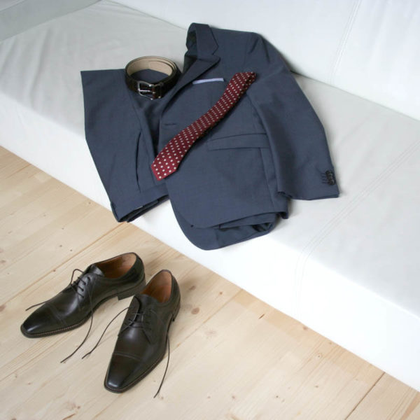 Photo men`s business shoes-Sophisticated design-dark brown mocha tone-2 shoes with a blue suit on a couch