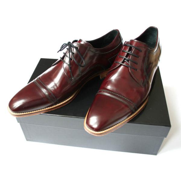 Foto stilsicherer Begleiter _Herrenschuh_Business_Derby_Captoe_poliert_Bordeaux_2 Schuhe auf schwarzem Schuhkarton