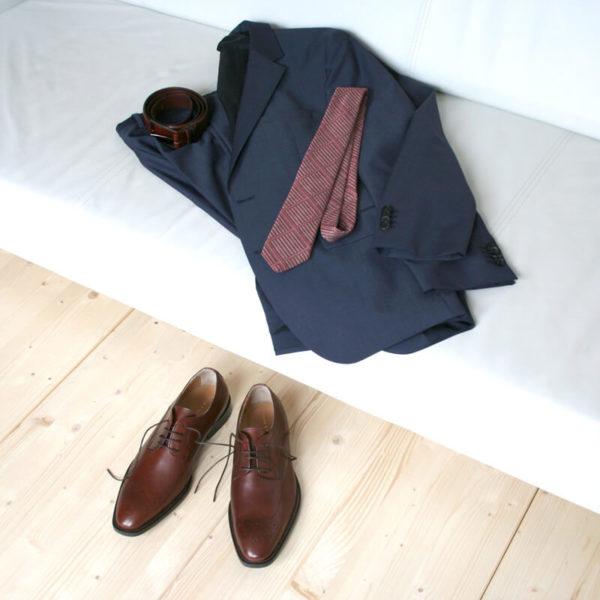 Foto-Nussbraune Business Herrenschuhe_auf Holzboden-dabei Anzug, Krawatte und Gürtel auf Couch