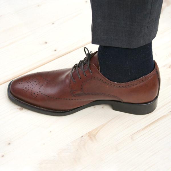 Foto-Nussbraune Business Herrenschuhe_Ein Schuh mit hochgezogenem Hosenbein nach links weisend