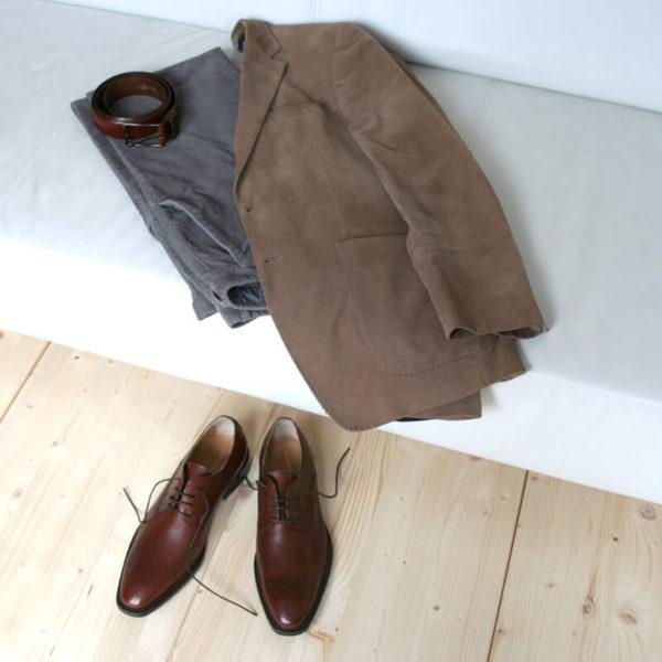 Foto-Nussbraune Business Herrenschuhe_auf hellem Holzfußboden abgestellt, dahinter graue Hose, hellbraunes Jacket und nussbrauner Gürtel