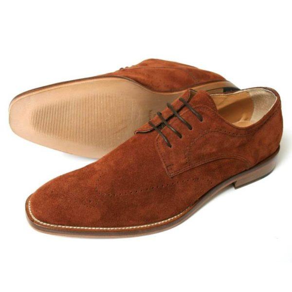 Foto: Zwei cognacfarbene Rauleder Herrenschuhe mit dezenter Verzierung, breiter Sohle und heller Naht. Modell: Lässige Eleganz. Beide Schuhe zeigen nach links. Ein Schuh liegt auf der Seite, so dass die Sohle zu sehen ist.