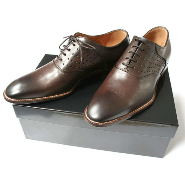 Foto: Zwei mokkafarbene Oxford Herrenschuhe mit Lochdekoration auf schwarzem Schuhkarton. Modell Dezent-modisch