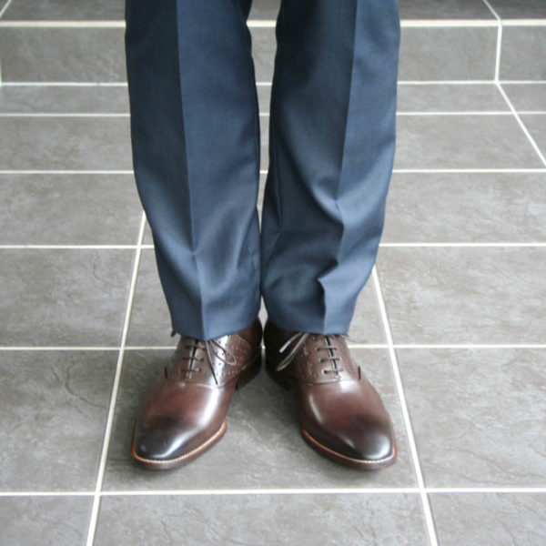 Men`s business shoes-Discreet fashionable-Oxford_with hole pattern_mocha brown_2 shoes with blue suit - only legs - front view