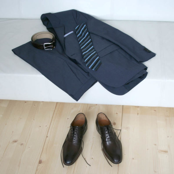 Men`s business shoes-Discreet fashionable-Oxford_with hole pattern_mocha brown_2 shoes in combination with a blue suit on a couch