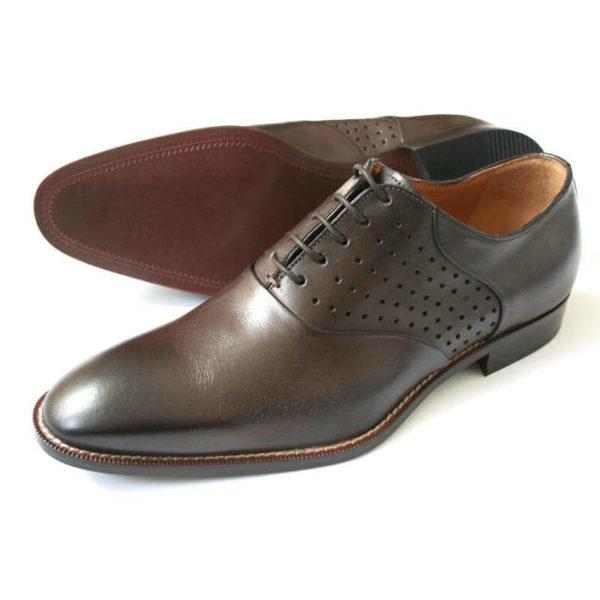 Foto: 2 mokkafarbene Oxford Herrenschuhe mit Lochverzierung. Beide Schuhe nach links zeigend. Einer liegend, so dass die Sohle zu sehen ist. Modell Dezent-modisch