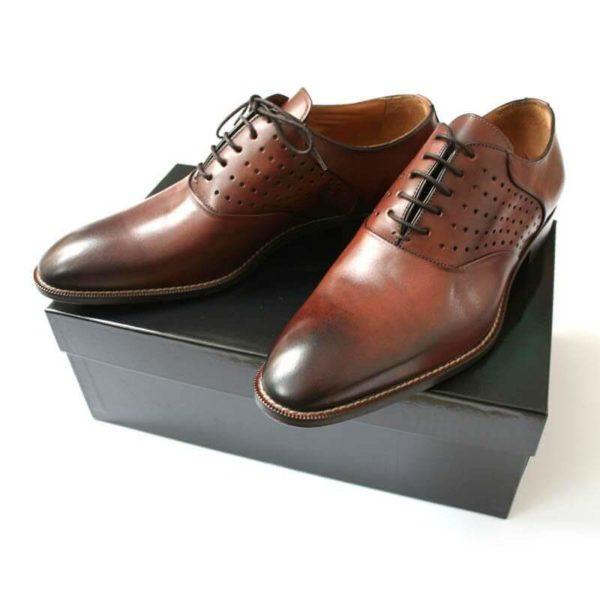 Foto Sportlich elegant: Herrenschuh_Business_Oxford_plain_Lochverzierung. 2 Schuhe auf schwarzem Schuhkarton.