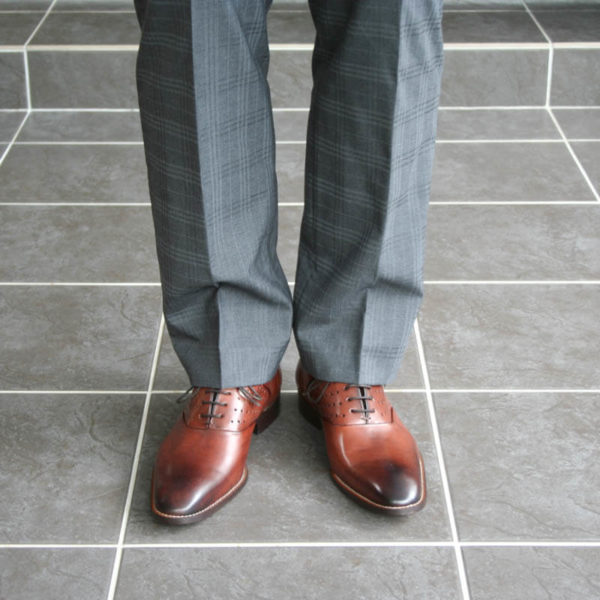 Photo-Men`s business shohes-Sporty elegant-_Oxford_in Cognac with hole pattern_2 shoes with gray suit - only legs-front view