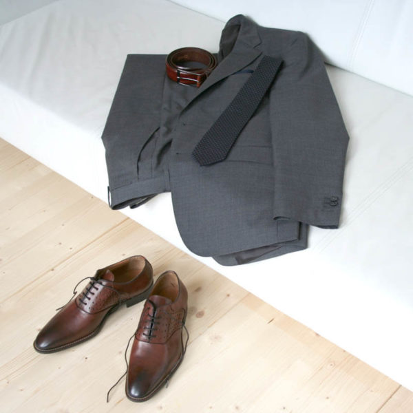 Photo-Men`s business shohes-Sporty elegant-_Oxford_in Cognac with hole pattern_2 shoes with a dark gray suit on a couch