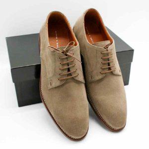 Foto zeigt zwei Herrenschuhe taupe aus Rauleder, die an einen schwarzen Schuhkarton gelehnt sind_Modell 374