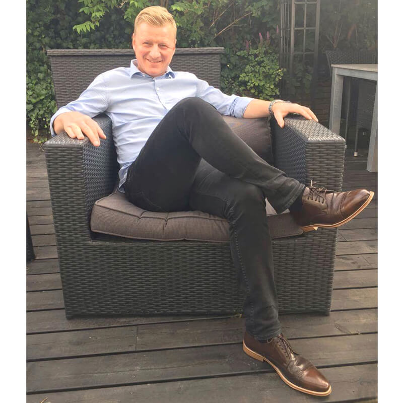 Foto: Mann sitzend auf Terrasse in einem Outdoor-Sessel mit hellblauem Oberhemd und schwarzer Hose dazu braune Herrenschuhe Komfortabler Klassiker